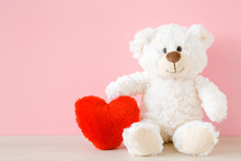 Smiling White Teddy Bear Sitting And Holding Red Soft Heart At Pastel Pink Wall. Front View. Closeup.