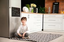 Little Boy Near Chalkboard On Refrigerator In Kitchen