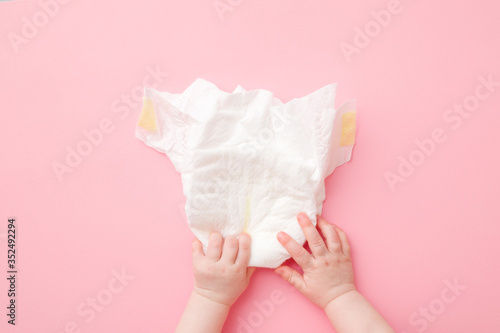 Baby hands touching white diaper on light pink table background Poster Mural XXL