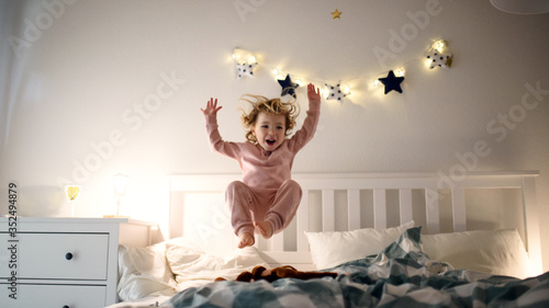 Obraz Two small children jumping on bed indoors at home, having fun. - fototapety do salonu