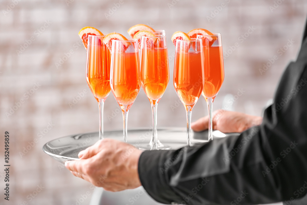 Fototapeta Waiter with glasses of tasty mimosa cocktail at banquet