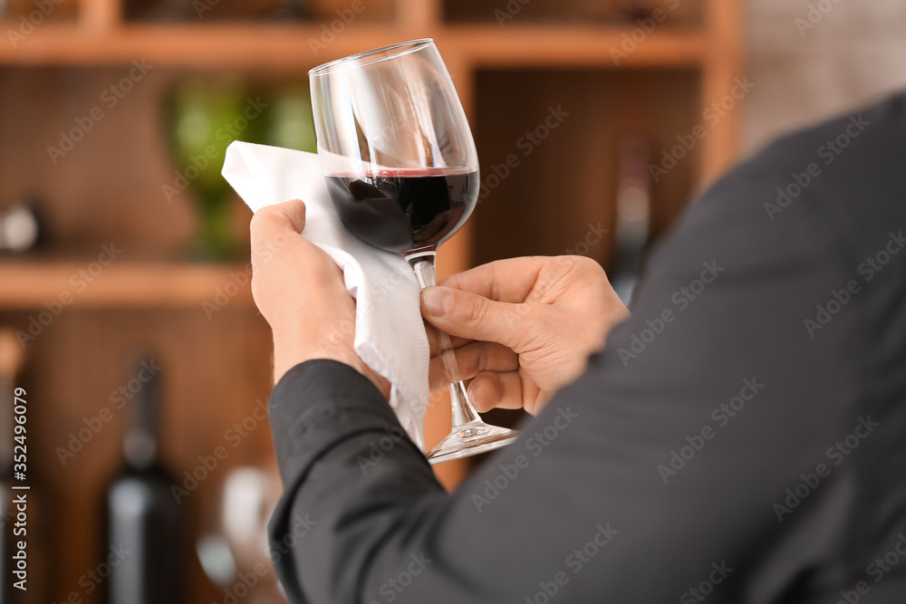 Fototapeta Man with glass of tasty wine and napkin in cellar
