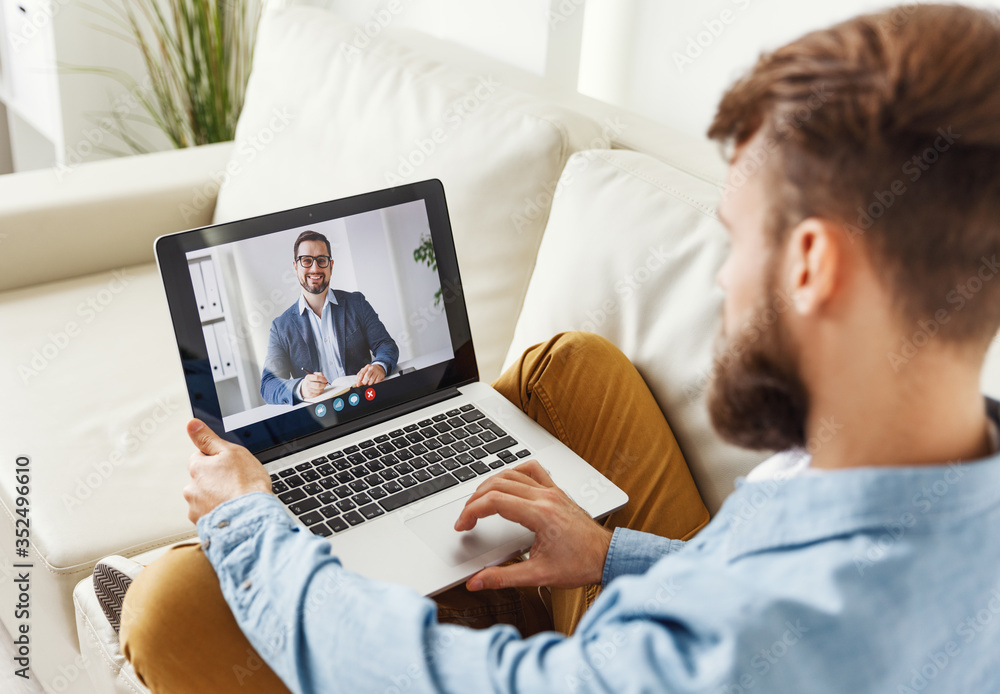 Fototapeta Man speaking with online financial counselor.