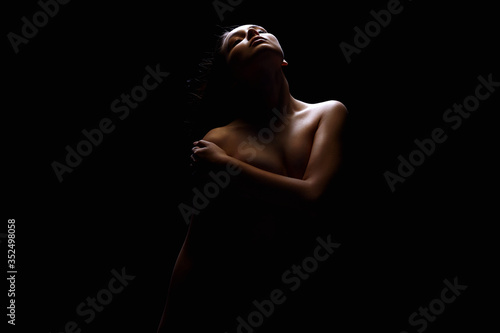 Nude Woman. Female silhouette under light in the dark