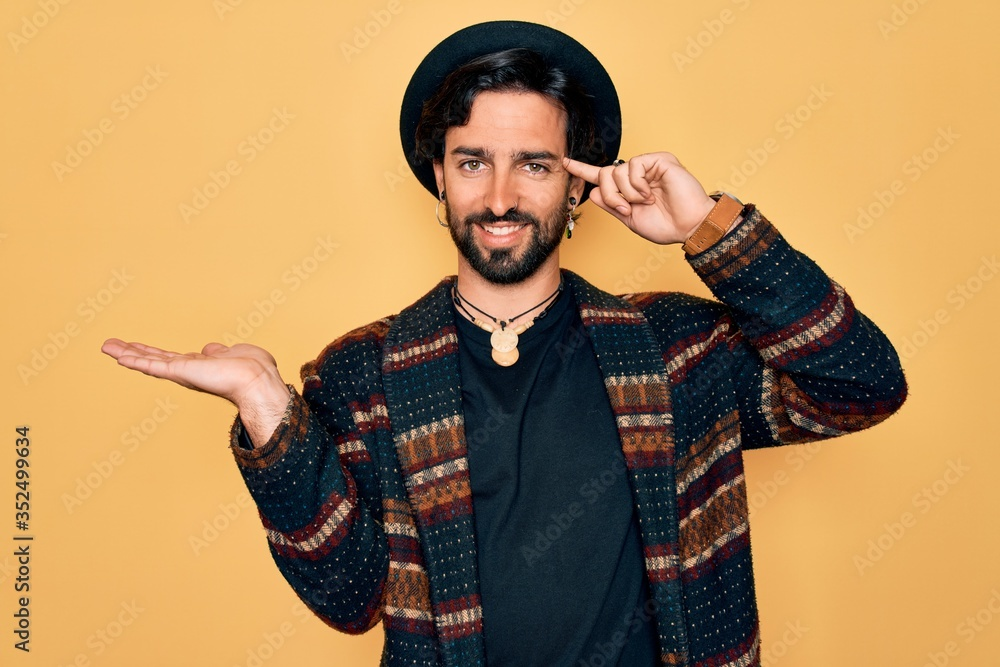 Fototapeta Young handsome hispanic bohemian man wearing hippie style and boho hat confused and annoyed with open palm showing copy space and pointing finger to forehead. Think about it.