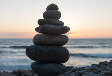 Stack Of Pebbles At Beach Against Sky During Sunset