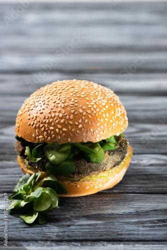 Obraz na plátne tasty vegan burger with microgreens served on wooden table
