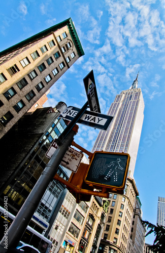 Платно Low Angle View Of Information Signs By Empire State Building Against Sky In City