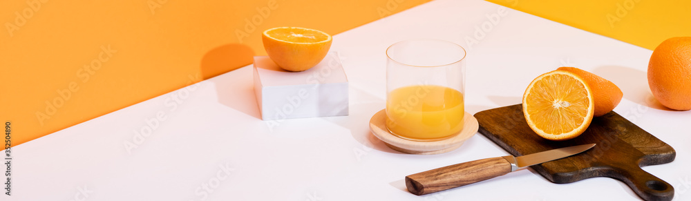 Fototapeta fresh orange juice in glass near ripe oranges, wooden cutting board with knife on white surface on orange background, panoramic shot