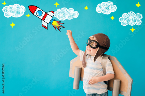 Happy child playing with toy paper wings against blue background Fototapeta