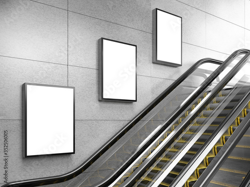 Photographie Side view of escalator on wall background with three blank light box