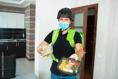 The food deliveryman is looking at the camera in the house Fotobehang
