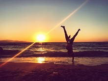 Silhouette Man Doing Handstand At Beach Against Sky During Sunset