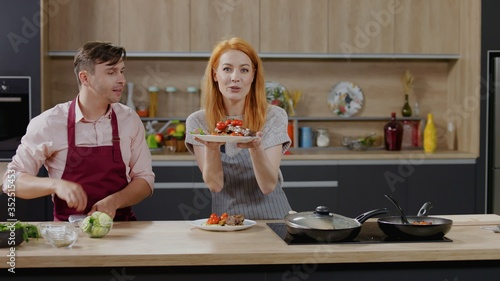 Fototapeta Cooking show hosts chefs, male and female, showing cooked dish into camera. Morning TV cooking programme obraz