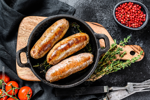 Photo Pork sausages in a cast-iron pan. Black background. Top view