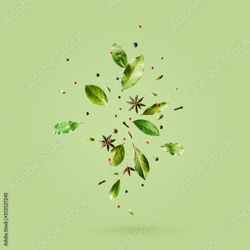 Fotografija Creative mockup with flying various types of spices Bay leaf, red pepper, anise on green background with copy space