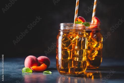 Fototapeta Glass of peach or apricot iced tea with fruit slices against dark blue background obraz