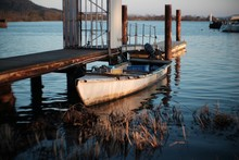 Lone Boat Moored At Jetty In Calm Lake