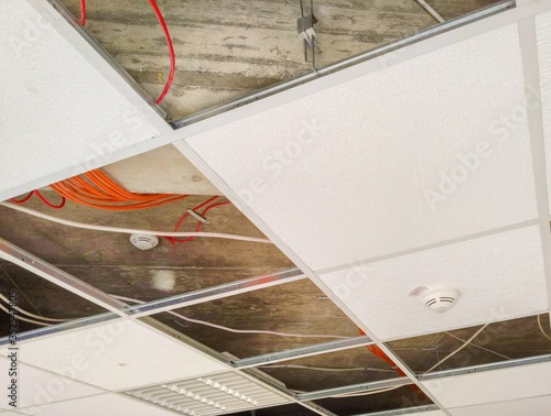 Photo Partially open suspended ceiling, with plenum area and wires visible above acous