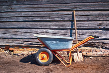 Garden Tools Stand On The Ground Next To An Old Wooden Shed On A Sunny Day. Metal Garden Wheelbarrow With A Shovel, Selective Focus