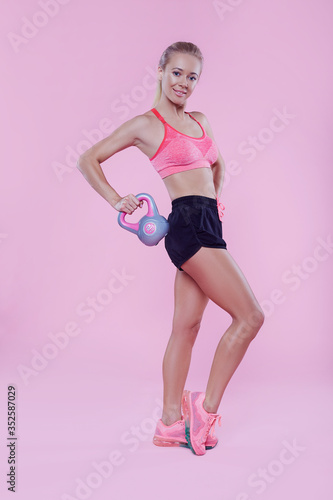 Fotomural Sexy sporty lady with weight studio portrait on pink background, fitness sporty woman beautiful fit girl, weight loss