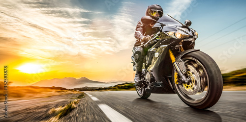 Fototapeta motorbike on the road riding. having fun riding the empty highway on a motorcycle tour / journey obraz