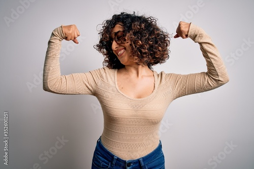 Young beautiful curly arab woman wearing casual t-shirt and glasses over white background showing arms muscles smiling proud Slika na platnu
