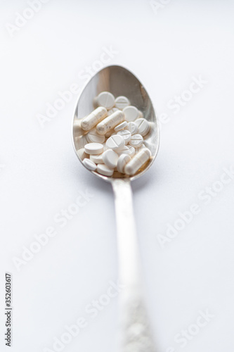 Vászonkép Medicine and health, treatment, pharmacy, coronavirus, pandemic, epidemic concept - layout one silver big tablespoon with different pills and capsules on a white background copy space