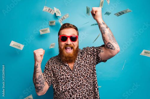 Obraz Photo of crazy handsome guy luxury rich person dollars fall from sky lottery cashback open mouth win big money raise fists wear leopard shirt sun specs isolated blue background - fototapety do salonu