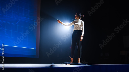 Fotografia On-Stage Successful Female Speaker Presents Technological Product, Uses Remote Control for Presentation, Showing Infographics, Statistics Animation on Screen