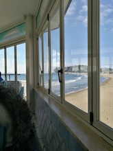 Scenic View Of Beach Against Sky Seen Through Glass Window