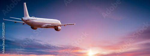 Obraz Commercial airplane jetliner flying above dramatic clouds in beautiful light. Travel concept. - fototapety do salonu