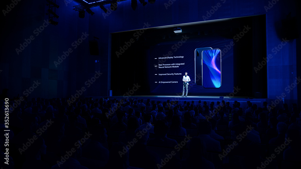 Fototapeta Live Event with Brand New Products Reveal: Keynote Speaker Presents Smartphone Device to Audience. Movie Theater Screen Shows Mock-up Touch Screen Phone with High-Tech Features and Top Highlights