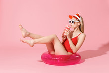 Beautiful Young Blonde Woman In Red One-piece Swimsuit Cap Sunglasses Isolated On Pink Background. People Summer Vacation Rest Lifestyle Concept. Sit In Swim Inflatable Ring Hold Cup Of Cola Or Soda.