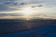 the golden sun across the wide open salt landscape in the great salt lake basin.