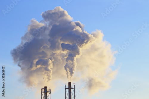 Tela Low Angle View Of Chimneys Emitting Smoke Against Clear Sky