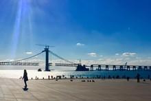People On Promenade Against Blue Sky