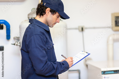 Obraz Technician servicing an hot-water heater - fototapety do salonu