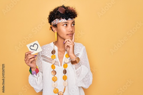 Obraz Beautiful african american afro hippie woman wearing sunglasses holding reminder with heart serious face thinking about question, very confused idea - fototapety do salonu