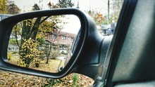 Close-up Of Trees And Houses Reflecting On Car Side-view Mirror