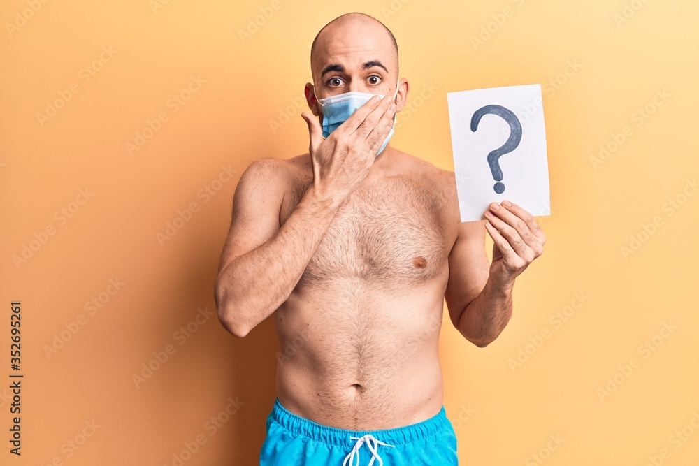 Fototapeta Young handsome bald man wearing swimwear and medical mask holding question mark covering mouth with hand, shocked and afraid for mistake. surprised expression