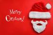 Leinwandbild Motiv Text MERRY CHRISTMAS and Santa Claus hat with beard on red background, flat lay