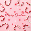 Leinwandbild Motiv Flat lay composition with text MERRY CHRISTMAS and candy canes on pink background