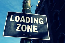 Low Angle View Of Loading Zone Text On Signboard In City