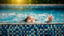 Baby Girl Drowning In Pool. Danger And Children Concept. Pools And Swimming Lessons.