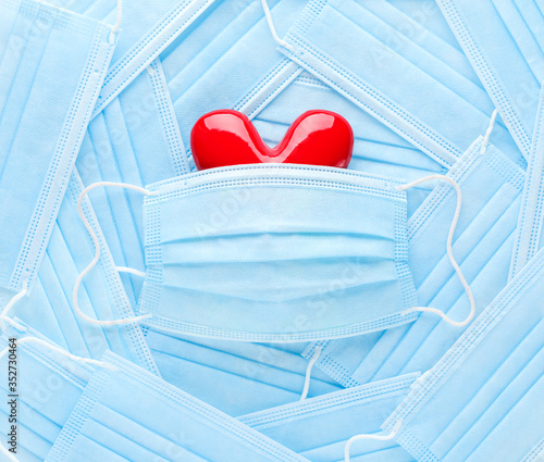 Obraz Bright red heart on a pile of medical face masks. Concept of support, love, care and a thank you to the frontline essential workers and healthcare workers. - fototapety do salonu