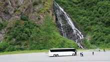 Tourists From A Tour Bus Explore The Area Around A Large Rushing Waterfall Off Cliff Side.