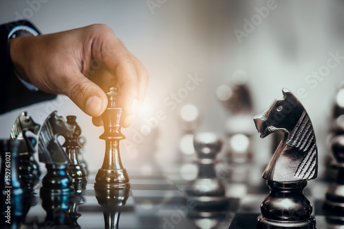 Fotografia Businessman moving chess piece and think strategic to win game