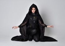 Fantasy Portrait Of A Woman With Red Hair Wearing Dark Leather Assassin Costume With Long Black Cloak.  Full Length Kneeling Pose, Isolated Against A Studio Background.