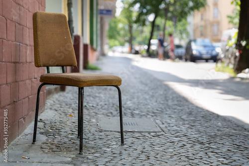 Carta da parati Empty Chair On Sidewalk By Brick Wall